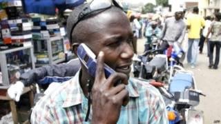 नाइजीरिया में मोबाइल पर बात करता शख्स