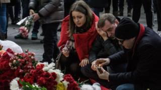 Люди у мемориала из цветов в Пулково