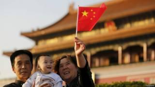 中國父母與孩子在天安門前舉著五星旗。