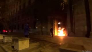 Скриншот с видео: Павленский на фоне горящей двери