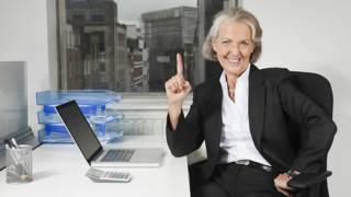 Улыбающаяся пожилая женщина за офисным столом