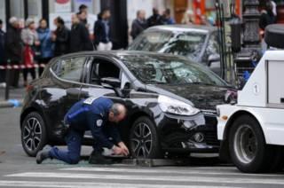 Полицейский собирается буксировать машину, оставленную подозреваемыми в пятничных нападениях