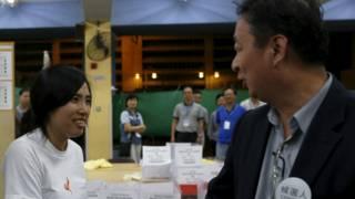 """""""青年新政""""成员邝葆贤(图左)与竞争者资深区议员刘伟荣(图右)握手。"""