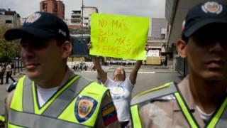 Policías venezolano delante de un cartel de protesta