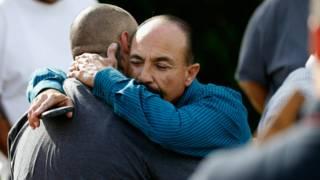 Dos personas se abrazan afuera del edificio donde se produjo el tiroteo.
