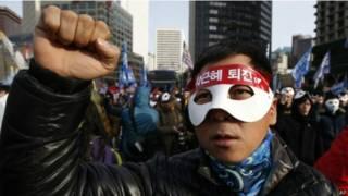 Участник акции протеста в Сеуле 5 декабря 2015 г.