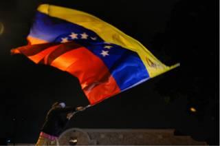 Челоек, размахивающий флагом Венесуэлы