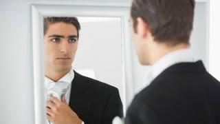Очень серьезный молодой человек перед зеркалом