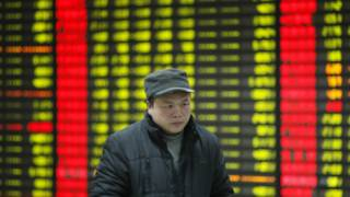 Một nhà đầu tư Trung Quốc với những tấm bảng giá cổ phiếu