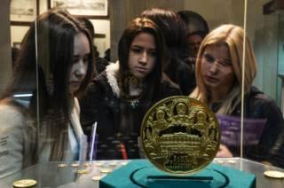 Девочки рассматривают монеты