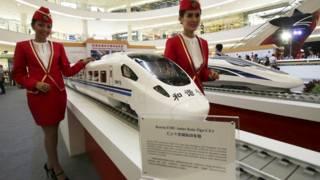 身穿雅玩高鐵乘務員制服的女士展示高鐵列車模型(資料圖片)