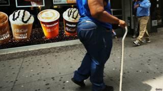 Женщина с ожирением и диабетом идет по улице
