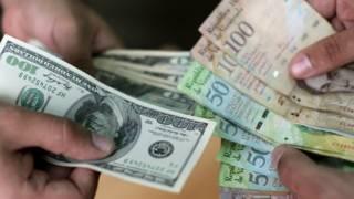 Billetes de dólares y de bolívares
