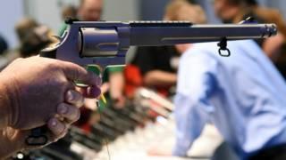 Imagen de una mano que empuña un revolver