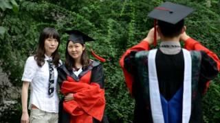 Un joven vestido con toga y birrete toma una foto a otra graduanda china.