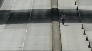 Hombre en carretera sin coches (foto de archivo)