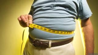 Hombre obeso midiendo su cintura