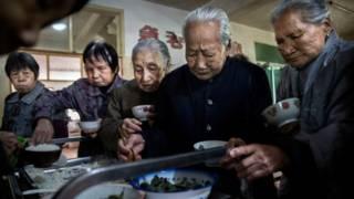 Ancianas chinas se sirven comida en una residencia para mayores