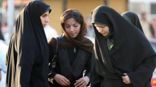 """Dos mujeres de la """"policía moral"""" de Irán advierten a una ciudadana."""