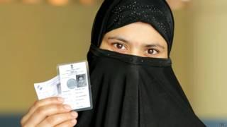 मतदाता पहचान पत्र दिखाती एक महिला.