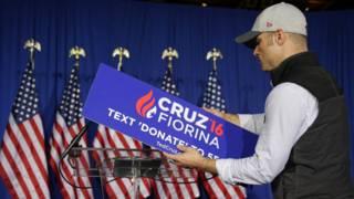 Un hombre retira el cartel de Ted Cruz y Carly Fiorina