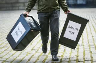 Человек несет урны для голосования в Эдинбурге