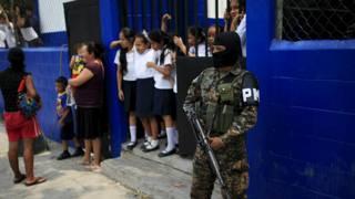 Un policía armado custodia la entrada de una escuela primaria en San Salvador