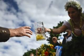 Официант приносит пиво на Октоберфесте