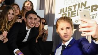 Justin Bieber tomándose una selfie con sus fans en un evento
