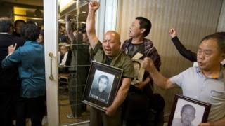 勞工遺屬在新聞發佈會上手持受害者遺像高叫口號