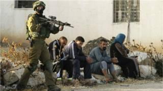 جندي إسرائيلي يصوب بندقيته تجاه فلسطينيين من يطا