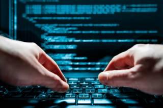 Компьютер и работающий за ним хакер