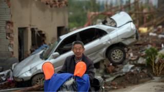 一名村民在損毀的房屋和汽車前