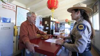 關敏在他的小餐館內與公園巡警聊天(2011年)
