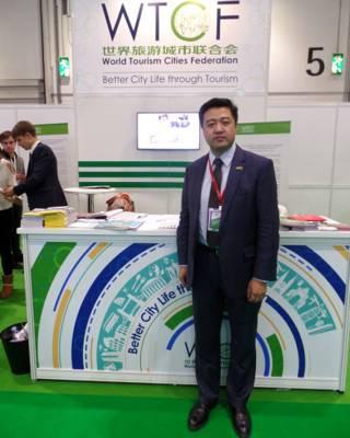 严晗在世界旅游城市联合会展台前(摄影:子川)