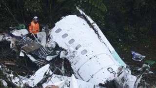 救援人员在坠毁的飞机残骸旁边