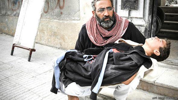 Foto de un padre con su hijo herido tomada por John Cantlie