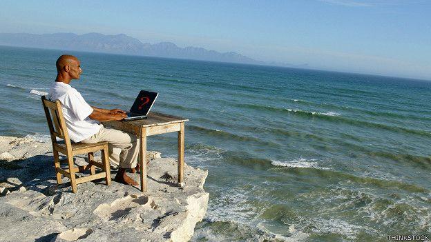 Hombre con una computadora frente al mar