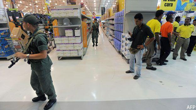 Guardias vigilan en las gondolas de supermercado venezolano semi vacías por la escasez de productos.