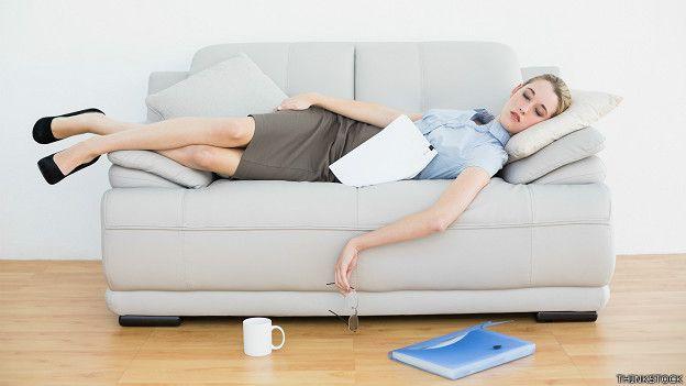 Executive goes to sleep, exhausted, on a sofa