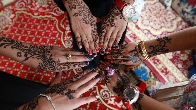 Jóvenes yemeníes muestran sus manos decorados con la tradicional henna