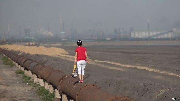 Mujer sobre una tuberia en el lago Baotou