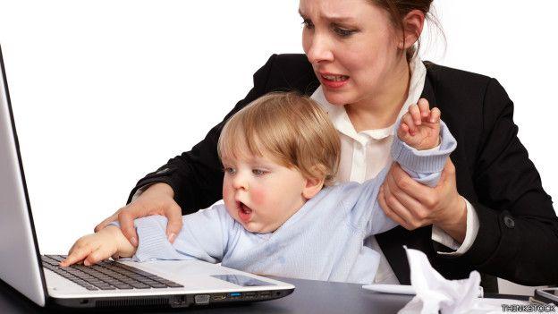 Una madre luchando con su pequeño para usar una laptop
