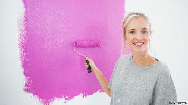 Una mujer pintando una pared