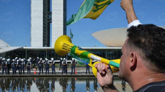 Un manifestante reclama frente al Congreso brasileño, custodiado por policías.