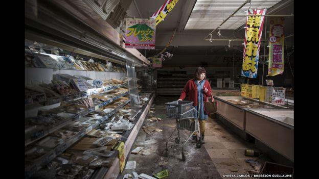Esta imagen fue tomada por Carlos Ayesta y Guillaume Bression. Muestra a una extrabajadora de un supermercado, ahora abandonado, volviendo a ver los restos que quedaron tras la catástrofe de Fukushima, Japón.