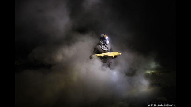 """En Kawah Ijen, un cráter volcánico de Indonesia, Lpan, un minero de 27 años, busca pedazos de """"oro del diablo"""" bajo los humos tóxicos en una fotografía de Luca Catalano Gonzaga."""