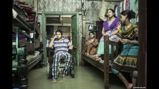 Una familia ve televisión en Chittagong, Bangladesh, a la espera de que la inundación de la marea retroceda. Las mareas son cada vez más frecuentes, afectan a los hogares y negocios como muestra la imagen de Jashim Salam.