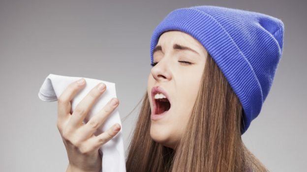 Una joven estornuda