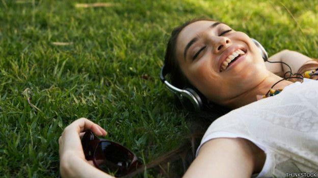 Una persona disfrutando de música echada en el pasto
